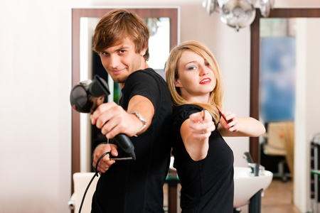 Two hairdresser - man and woman - posing for the camera in the hairdresser Stock Photo - 10428327