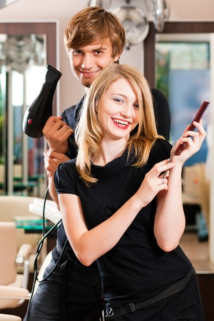 Two hairdresser - man and woman - posing for the camera in the hairdresser photo
