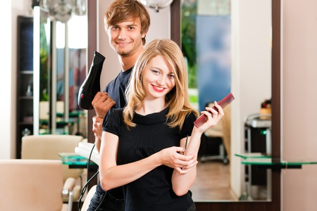 blow dryer: Two hairdresser - man and woman - posing for the camera in the hairdresser