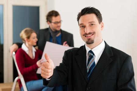 agente comercial: Pareja joven comprar o alquilar una casa o apartamento, que están cumpliendo con el propietario o agente de bienes raíces de pie frente