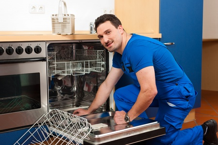 Technician or plumber repairing the dishwasher in a household