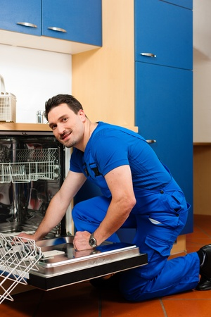 installer: Technician or plumber repairing the dishwasher in a household