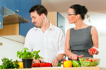 hombre cocinando: Pareja joven - hombre y una mujer - la cocina en su cocina en casa preparando las verduras para la ensalada y salsas para pasta