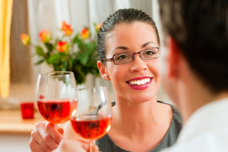 Young couple having romantic dinner - both drinking rose wine    photo