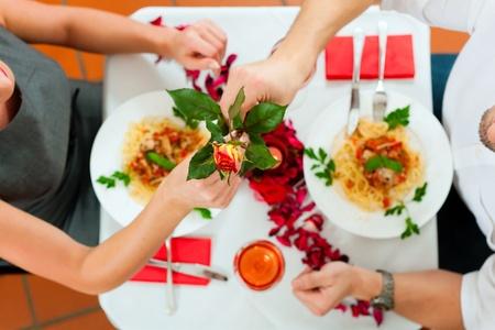femme romantique: Couple au déjeuner ou au dîner, il est de lui donner une rose
