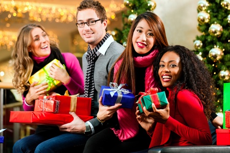 gift bag: Diversity group of four people - Caucasian, black and Asian - sitting with Christmas presents and bags in a shopping mall in front of a Christmas tree with baubles Stock Photo