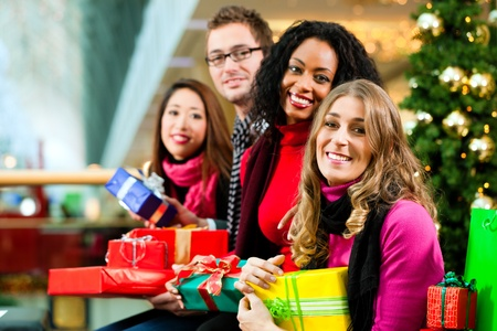 Diversity group of four people - Caucasian, black and Asian - sitting with Christmas presents and bags in a shopping mall in front of a Christmas tree with baubles Stock Photo - 10428074