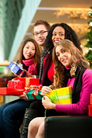 Diversity group of four people - Caucasian, black and Asian - sitting with Christmas presents and bags in a shopping mall in front of a Christmas tree with baubles Stock Photo - 10428080