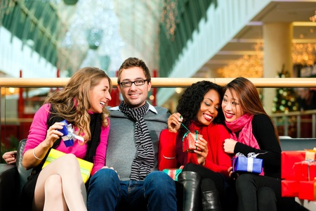 shopping man: Diversity group of four people - Caucasian, black and Asian - sitting with Christmas presents and bags in a shopping mall  Stock Photo
