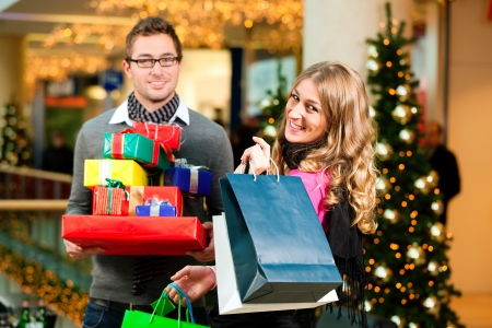 christmas shopping bag: Couple - Caucasian man and woman - with Christmas presents, gifts and shopping bags - in a mall in front of a Christmas tree