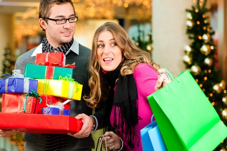 christmas shopping: Couple - Caucasian man and woman - with Christmas presents, gifts and shopping bags - in a mall in front of a Christmas tree