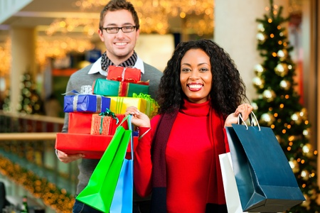 Couple - Caucasian man and black woman - with Christmas presents, gifts and shopping bags - in a mall in front of a Christmas tree photo