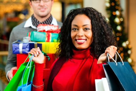 christmas shopping: Couple - Caucasian man and black woman - with Christmas presents, gifts and shopping bags - in a mall in front of a Christmas tree