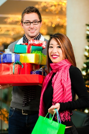 Couple - Caucasian man and Asian woman - with Christmas presents, gifts and shopping bags - in a mall in front of a Christmas tree Stock Photo - 10428073