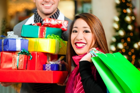 Couple - Caucasian man and Asian woman - with Christmas presents, gifts and shopping bags - in a mall in front of a Christmas tree photo
