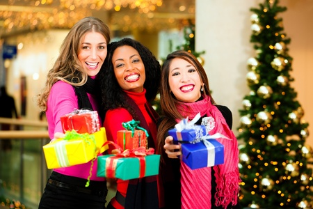 shopping mall: Group of three women - white, black and Asian - with Christmas presents in a shopping mall in front of a Christmas tree