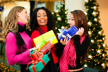 three presents: Group of three women - white, black and Asian - with Christmas presents in a shopping mall in front of a Christmas tree