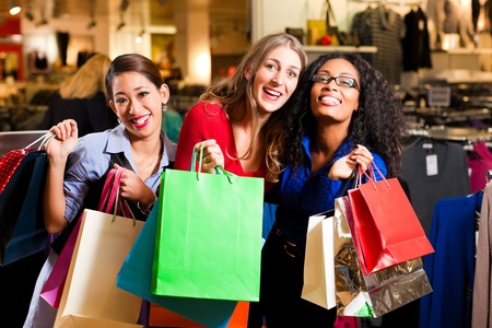asian american: Group of three women - white, black and Asian – shopping downtown in a mall Stock Photo