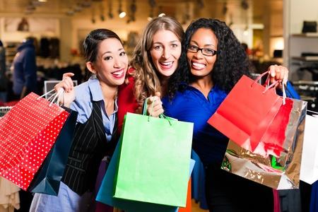 шопоголика: Группа из трех женщин - белые, черные и азиатские - торговый центр в торговом центре Фото со стока