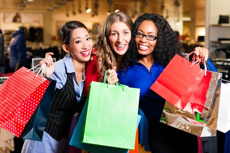 shopaholics: Group of three women - white, black and Asian – shopping downtown in a mall Stock Photo