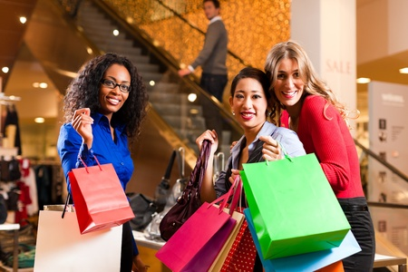 Group of three women - white, black and Asian – shopping downtown in a mall; in the background a man on escalator photo