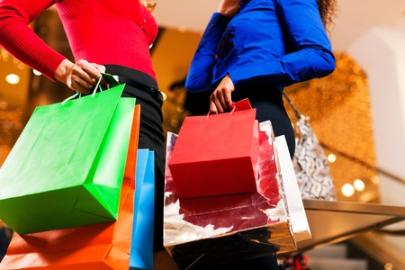 Two women in a shopping mall with colorful bags simply having fun photo
