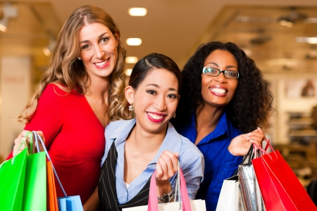 Group of three women - white, black and Asian – shopping downtown in a mall   photo