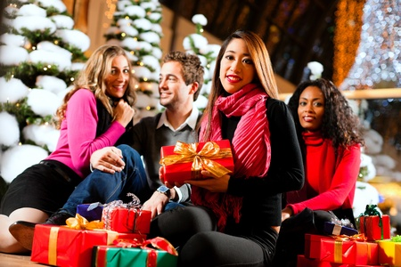 Group of four people - diversity - sitting amid artificial snow covered fir trees and lights with Christmas presents in a shopping mall photo