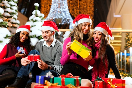 Group of four people - diversity - with Santa hats sitting amid artificial snow covered fir trees and lights with Christmas presents in a shopping mall photo