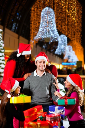 Santa Claus in male and female variants giving Christmas gifts in a shopping mall amid artificial snow covered fir trees and lights photo