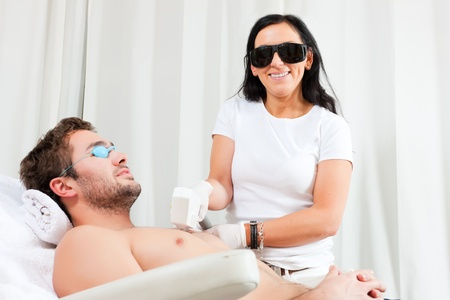 depilation: Man receiving waxing in a Day Spa; for protection he and the beautician wear specs