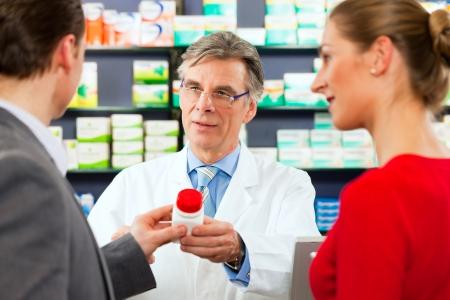 Pharmacist with customers in pharmacy photo