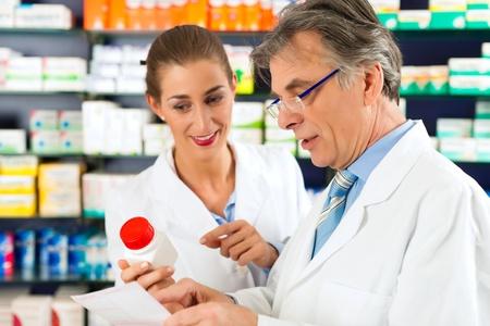 drugstore: Dos farmacéuticos con productos farmacéuticos de la mano de consultoría entre sí en una farmacia