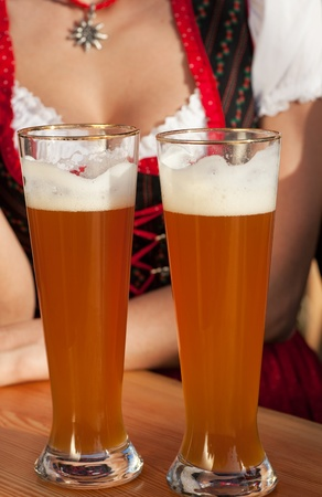 Paar in bayerischer Tracht - Dirndl und Lederhosen - in einem Bierzelt auf dem Oktoberfest oder im Biergarten genießen Sie ein Glas leckeren Weizenbier, nur Gläser und Oberkörper zu sehen