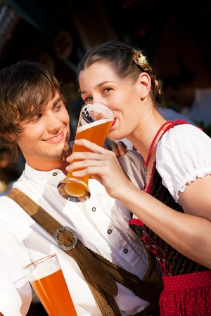 lederhosen: Couple in traditional Bavarian Tracht - Dirndl and Lederhosen - in front of a beer tent at the Oktoberfest or in a beer garden enjoying a glass of tasty wheat beer  Stock Photo