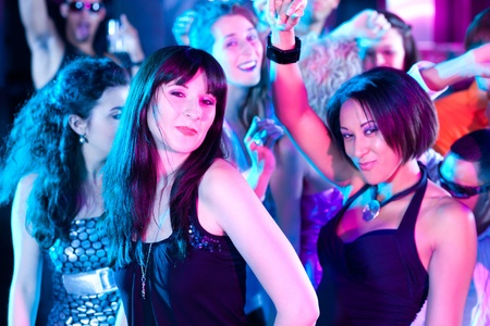 Dance action in a disco club - group of friends, men and women of different ethnicity, dancing to the music having lots of fun photo