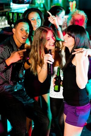jovenes tomando alcohol: Grupo de amigos - hombres y mujeres de diferentes etnias - divertirse en una discoteca o club nocturno