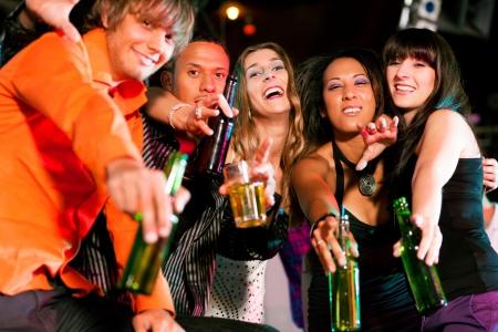 jovenes tomando alcohol: Grupo de amigos - hombres y mujeres de diferente etnia - divirtiéndose en una discoteca o club nocturno