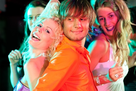 Group of friends dancing to the music in a disco club having lots of fun photo