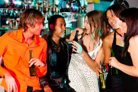 Gruppe von Freunden - M�nner und Frauen unterschiedlicher ethnischer Zugeh�rigkeit - Spa� in der Disco oder Nachtclub Lizenzfreie Bilder