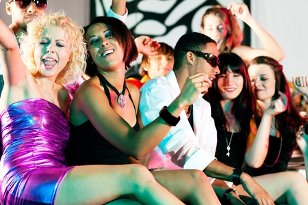 woman night: Group of friends - men and women of different ethnicity - having fun in a disco or nightclub