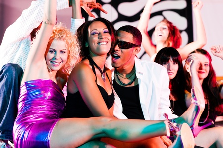 night club: Group of friends - men and women of different ethnicity - having fun in a disco or nightclub