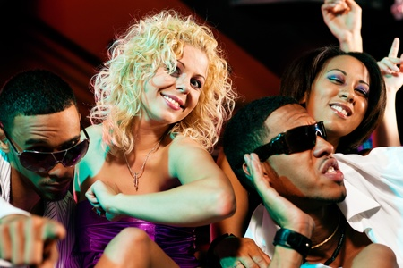 fiestas discoteca: Grupo de amigos - hombres y mujeres de diferente etnia - divirti�ndose en una discoteca o club nocturno