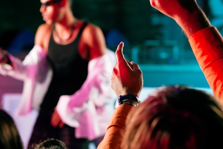 Rap or Hip-Hop Musicians performing on stage in a club in front of a cheering crowd photo