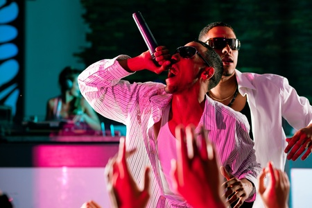 rapping: Rap or Hip-Hop Musicians performing on stage in a club in front of a cheering crowd Stock Photo