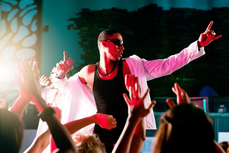hiphop: Rap or Hip-Hop Musicians performing on stage in a club in front of a cheering crowd Stock Photo