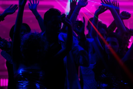 Silhouettes of dancing people having a celebration in a disco club, the light show is sending laser beams through the backlit scene Stock Photo - 10448760