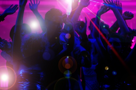 Silhouettes of dancing people having a celebration in a disco club, the light show is sending laser beams through the backlit scene Stock Photo - 10448764