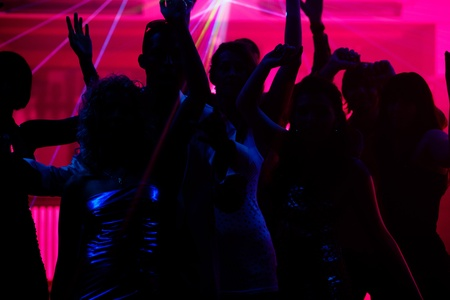 club scene: Silhouettes of dancing people having a celebration in a disco club, the light show is sending laser beams through the backlit scene Stock Photo