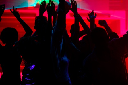 Silhouettes of dancing people having a celebration in a disco club, the light show is sending laser beams through the backlit scene Stock Photo - 10448762